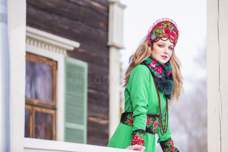 Muchacha rubia caucásica en vestido verde de moda y Kokoshnik con el modelo florido y las gotas Presentación contra casa de mader imagen de archivo libre de regalías