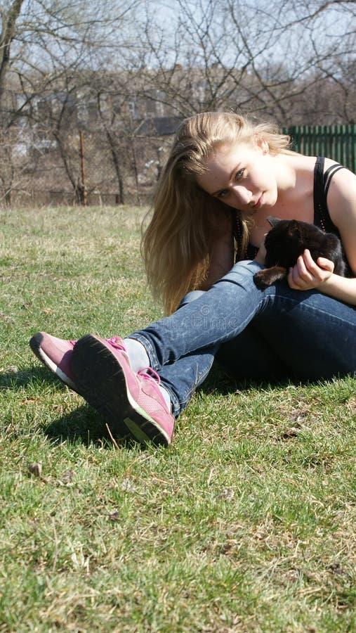Muchacha rubia con el gato negro fotos de archivo libres de regalías