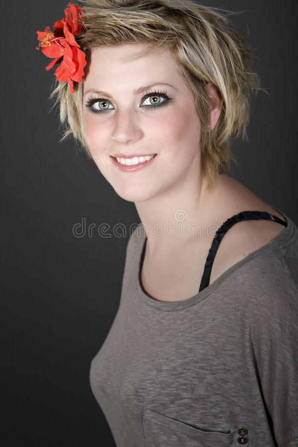 Muchacha rubia con la flor roja en su pelo foto de archivo libre de regalías