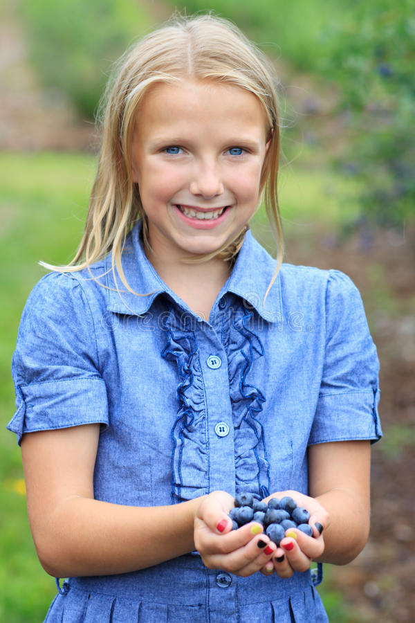 Muchacha rubia con la sonrisa escogida fresca de los arándanos fotos de archivo libres de regalías