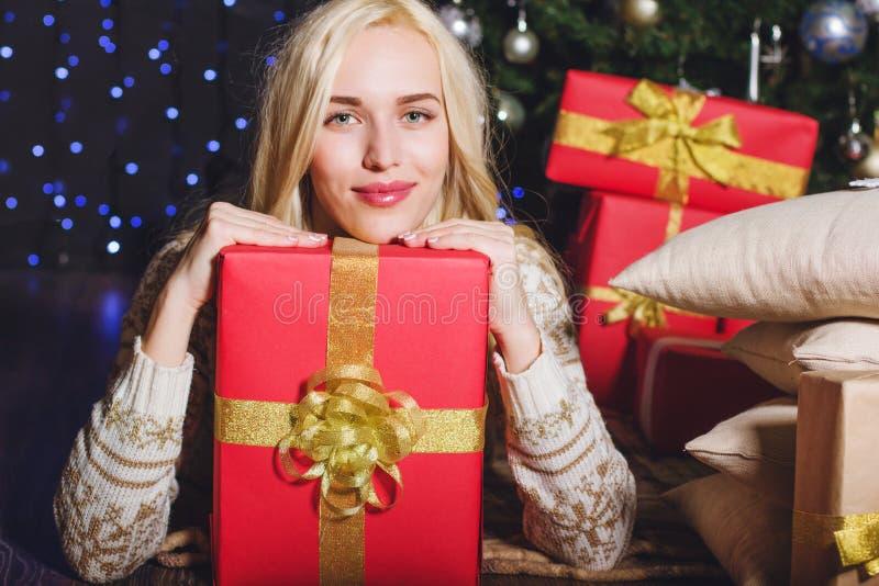 Muchacha rubia con las cajas de regalo rojas de la Navidad fotografía de archivo