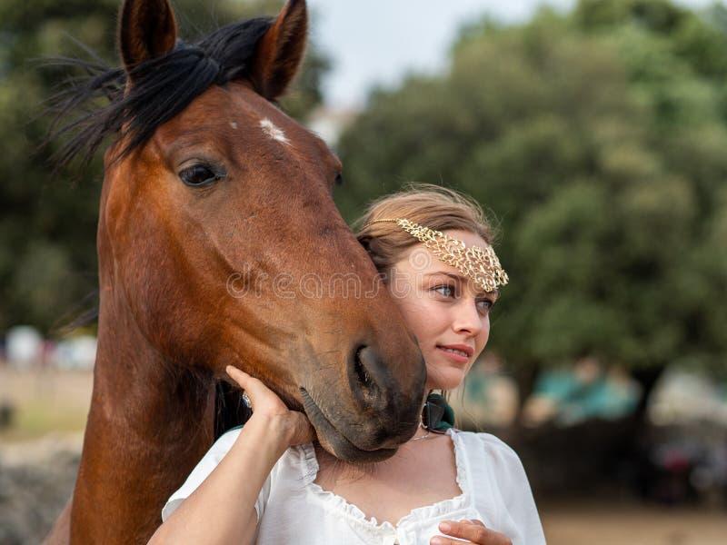 Muchacha rubia con los ojos azules y maquillaje con el duende en el campo con un caballo marrón y un cabo verde imagen de archivo