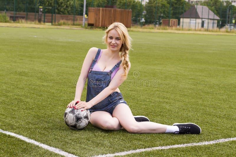 Muchacha rubia con una bola que se sienta en un campo de fútbol fotografía de archivo
