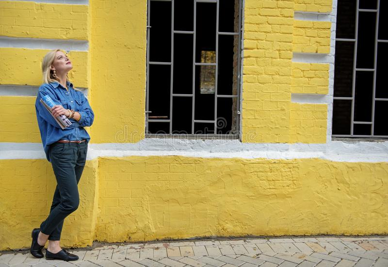 Muchacha rubia de Dreamful que se coloca cerca del edificio amarillo fotos de archivo libres de regalías