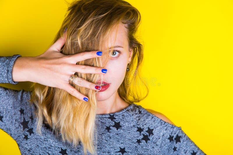 Muchacha rubia de moda con la manicura británica en fondo amarillo fotos de archivo