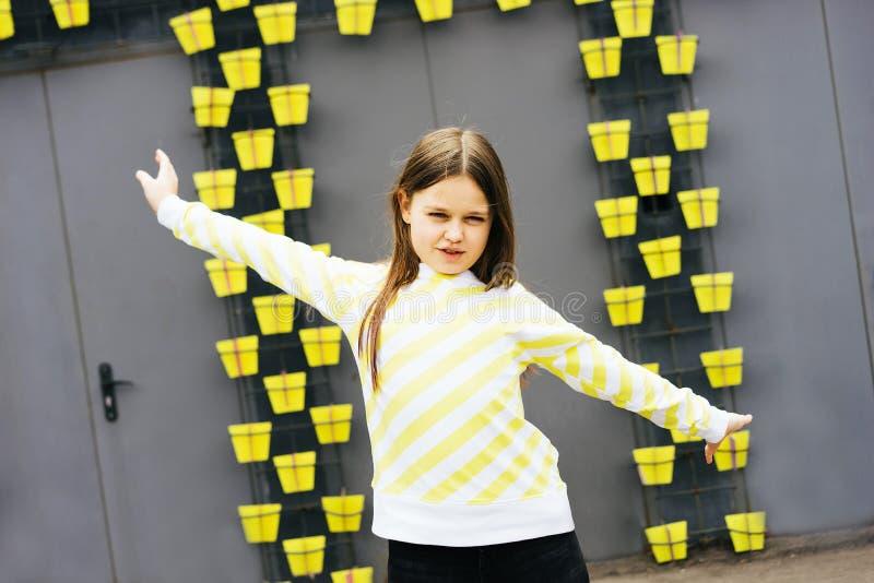 Muchacha rubia de pelo largo en un suéter amarillo y una chaqueta amarilla imagen de archivo