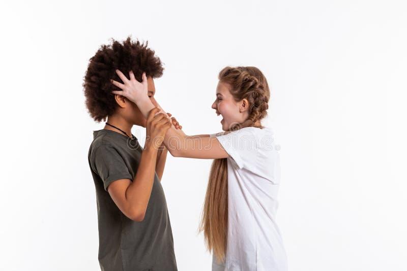 Muchacha rubia de pelo largo enojada que grita en su amigo confuso foto de archivo