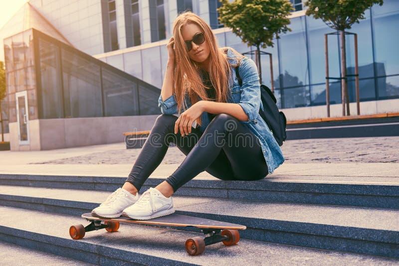 Muchacha rubia del inconformista joven en ropa casual y gafas de sol, sentándose en pasos contra un rascacielos, descansando desp imagen de archivo libre de regalías