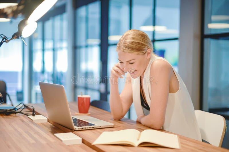 Muchacha rubia del negocio que escribe un libro y que llama por teléfono delante de un la foto de archivo