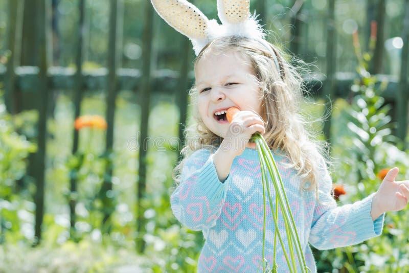 Muchacha rubia del niño en traje del conejito de pascua que roe la zanahoria fresca imagen de archivo