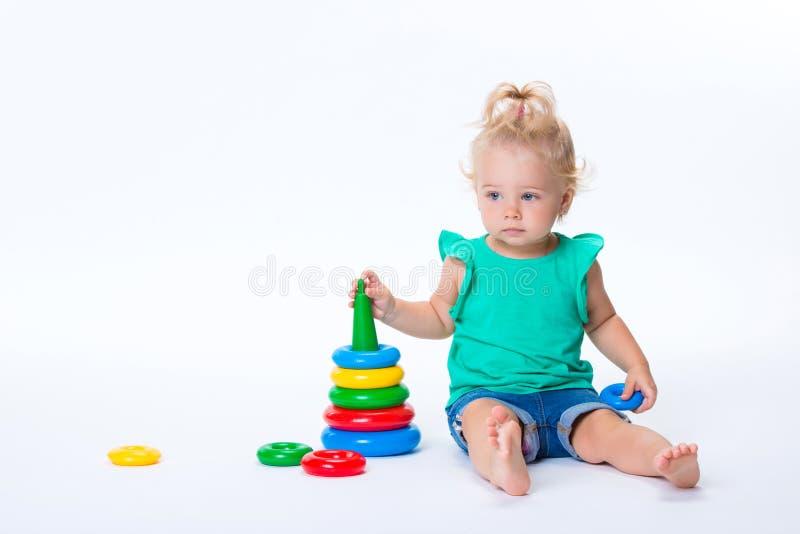 Muchacha rubia del niño lindo que juega con el juguete de la pirámide del color aislado en el fondo blanco Desarrollo feliz de la fotos de archivo