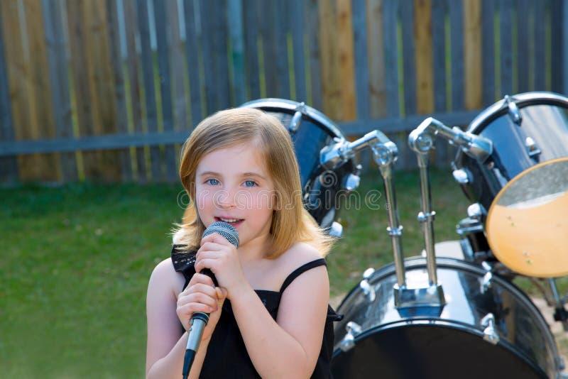 Muchacha rubia del niño que canta en patio trasero del tha con los tambores fotografía de archivo libre de regalías