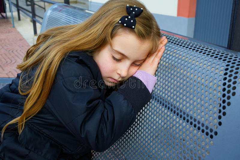Muchacha rubia del niño que finge siendo sueño en banco fotografía de archivo