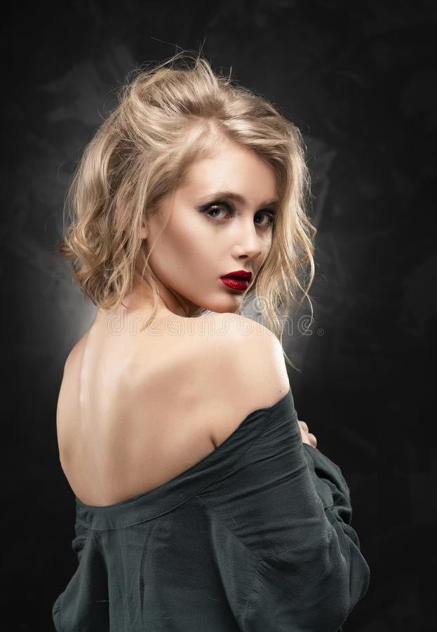 Muchacha rubia delgada braless joven hermosa con el pelo despeinado y el maquillaje agresivo, llevando una camisa desabrochada y  foto de archivo libre de regalías