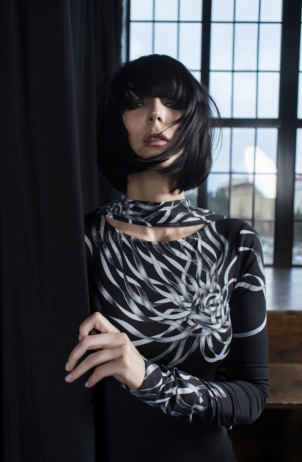 Muchacha rubia delgada patilarga que lleva un vestido apropiado oscuro corto y una situación morena de la peluca en las cortinas  imágenes de archivo libres de regalías