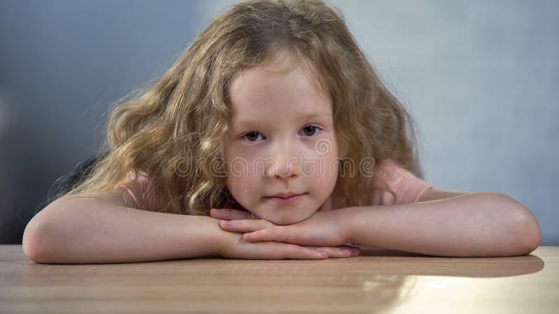 Muchacha rubia deprimida sola que se sienta solamente en la tabla, mirando a la cámara, adopción fotografía de archivo