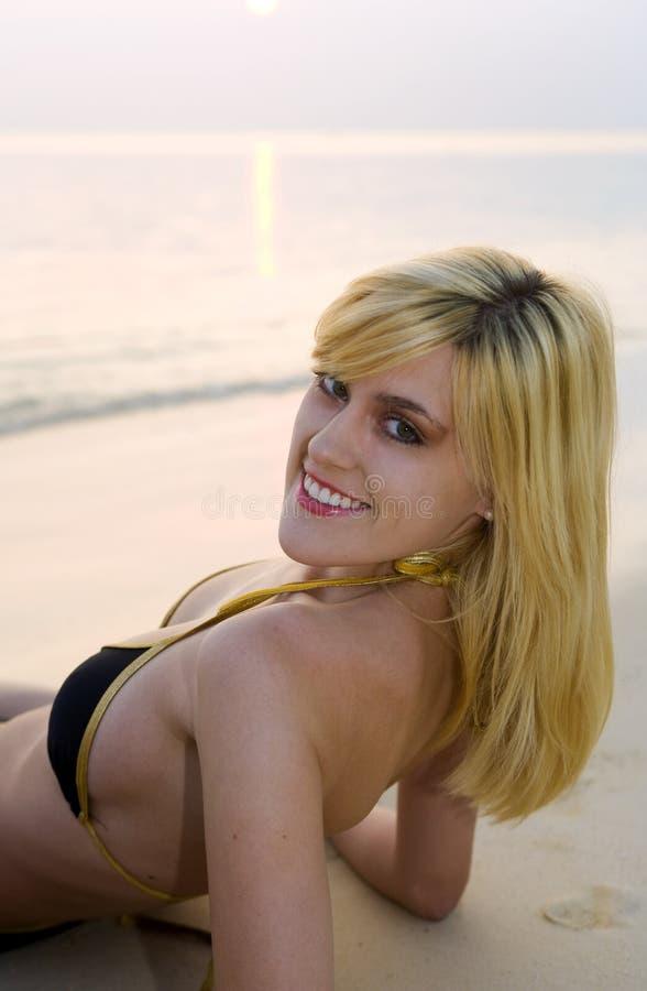 Muchacha rubia en bikiní en una playa en la salida del sol fotos de archivo libres de regalías