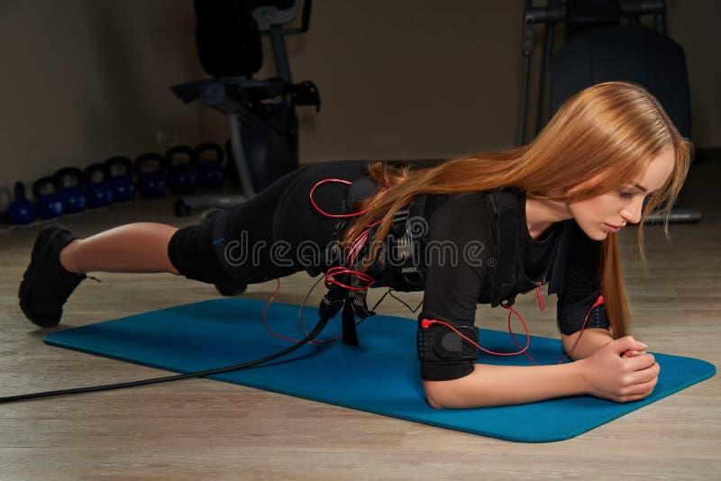 Muchacha rubia en el traje del ccsme que hace ejercicio del tablón en la estera de los deportes resplandor imagenes de archivo