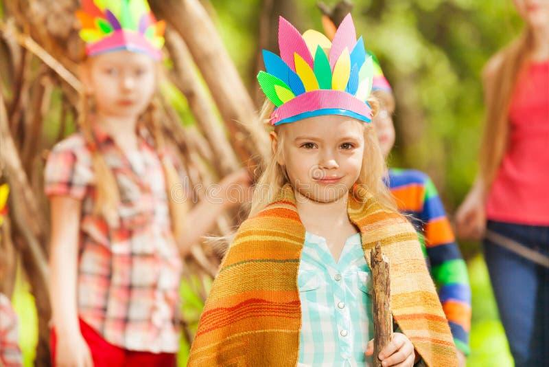 Muchacha rubia en el traje del ` s de Injun que juega con los amigos imagenes de archivo