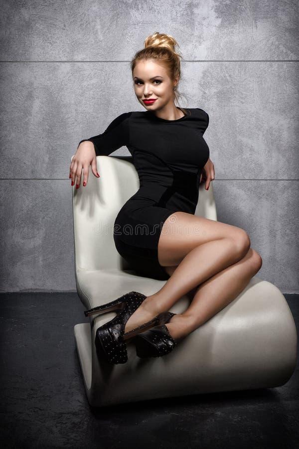 Muchacha rubia en el vestido negro que se sienta en la butaca blanca imágenes de archivo libres de regalías