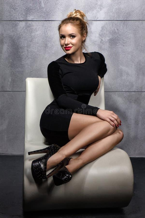 Muchacha rubia en el vestido negro que se sienta en la butaca blanca fotografía de archivo