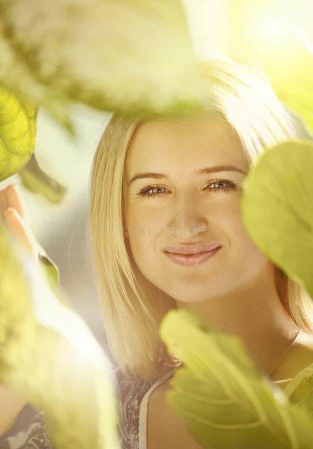 Muchacha rubia en hojas fotografía de archivo