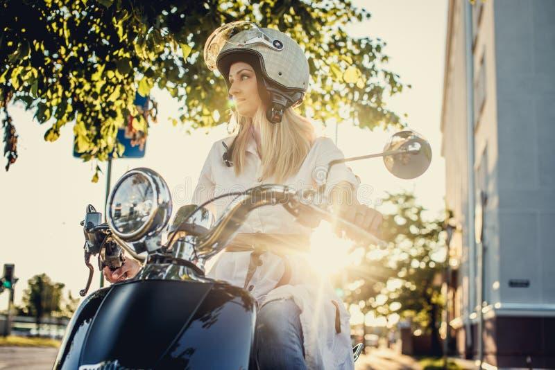 Muchacha rubia en la vespa del moto imágenes de archivo libres de regalías