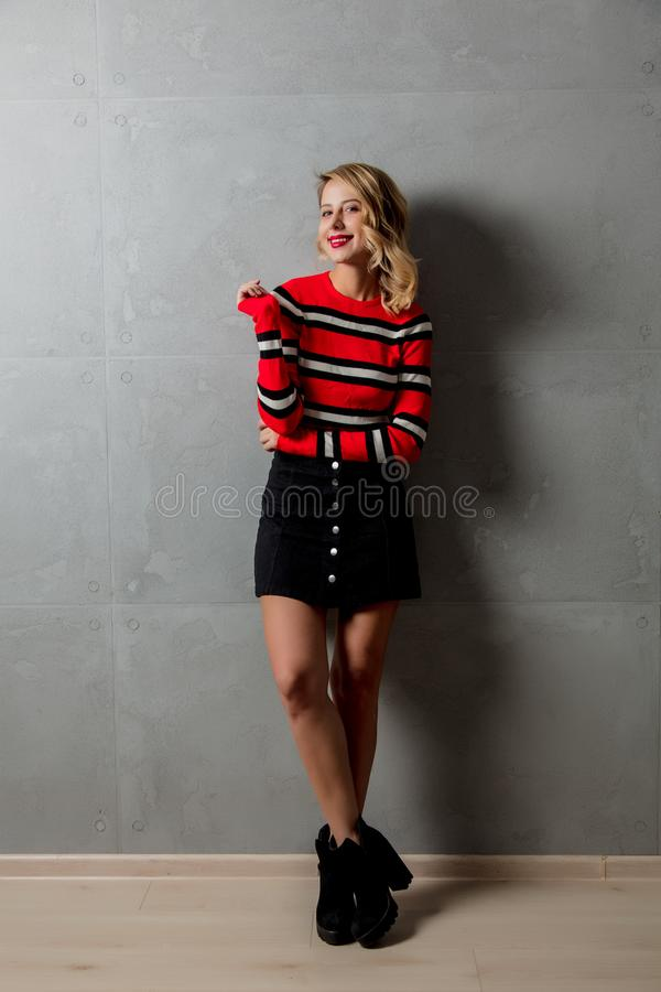 muchacha rubia en suéter rayado rojo imagen de archivo