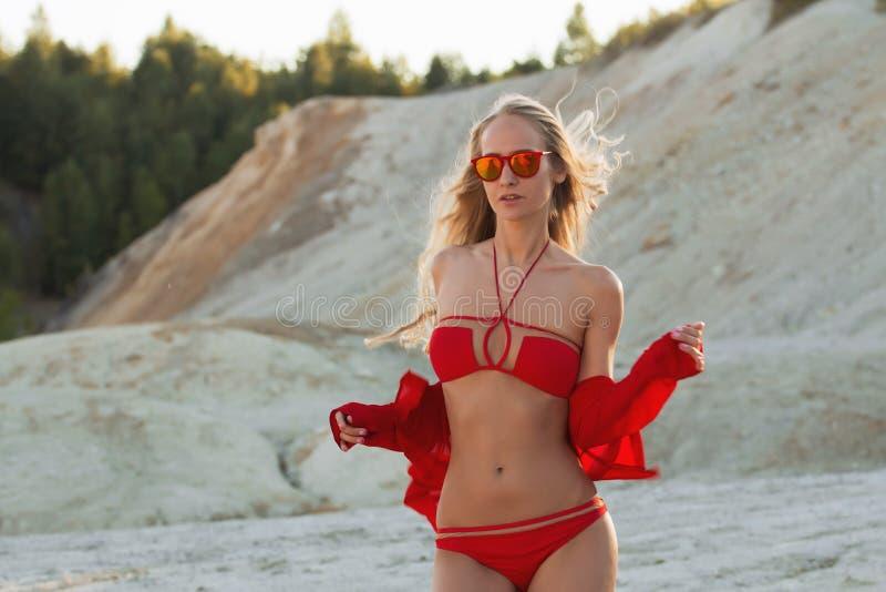 Muchacha rubia en traje de baño rojo en la playa fotografía de archivo