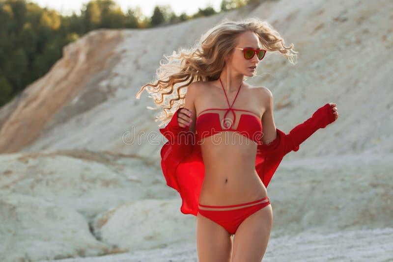 Muchacha rubia en traje de baño rojo en la playa fotos de archivo