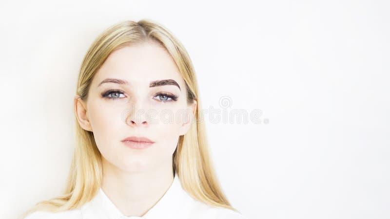 Muchacha rubia en un salón de belleza Fabricación de las cejas con alheña, antes y después Cuidado seguro de la cara foto de archivo
