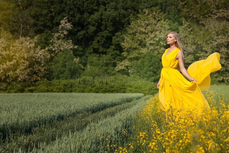 Muchacha rubia en un vestido amarillo fotos de archivo