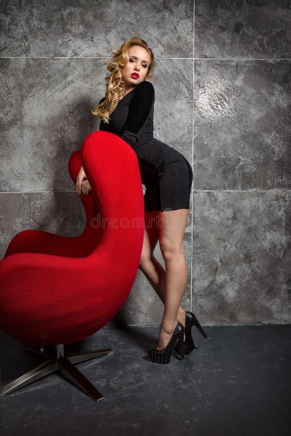 Muchacha rubia en un vestido negro que se coloca cerca de la butaca roja fotografía de archivo libre de regalías