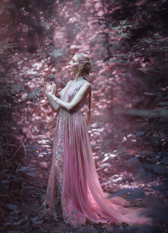 Muchacha rubia en un vestido rosado lujoso La bruja lleva a cabo magia en sus manos Peinado de Elven, trenza creativa imágenes de archivo libres de regalías