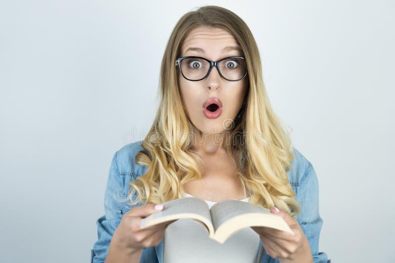 Muchacha rubia en vidrios sorprendida sosteniendo el libro imágenes de archivo libres de regalías