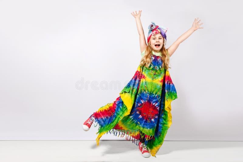 Muchacha rubia feliz del niño en vestido colorido del hippie contra la pared blanca imagen de archivo