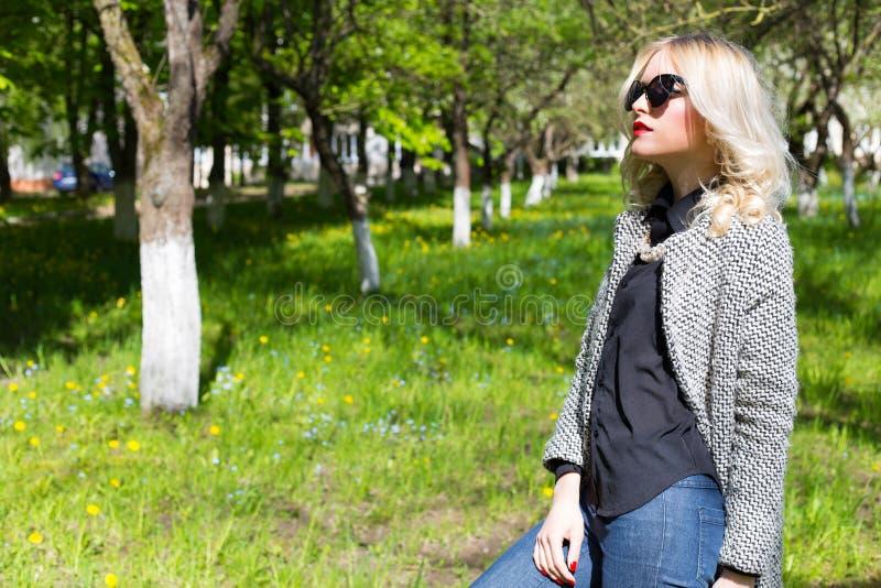 Muchacha rubia feliz joven hermosa en capa, vaqueros y gafas de sol caminando en el parque en un día soleado foto de archivo