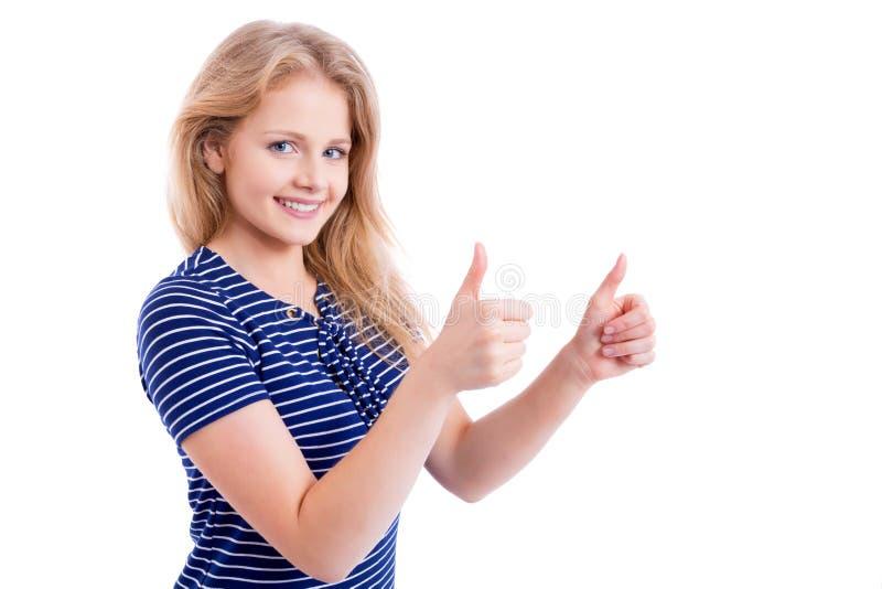 Muchacha rubia feliz que muestra MUY BIEN - los pulgares para arriba fotografía de archivo