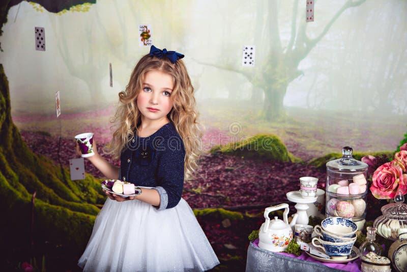 Muchacha rubia hermosa como Alicia en el país de las maravillas foto de archivo