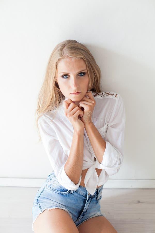 Muchacha rubia hermosa con los ojos azules que se sientan en el piso en una sala blanca 1 imagen de archivo