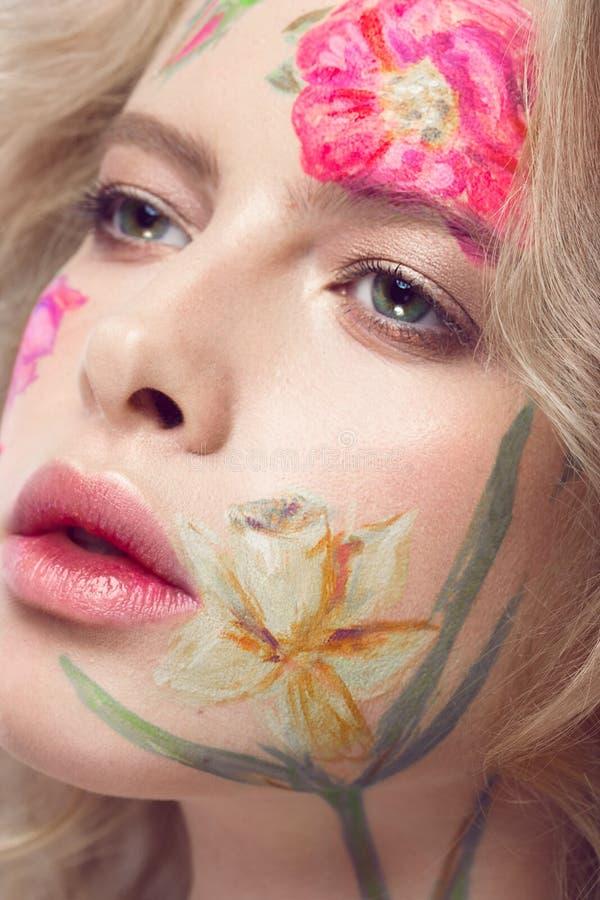 Muchacha rubia hermosa con los rizos y un estampado de flores en la cara Flores de la belleza fotos de archivo