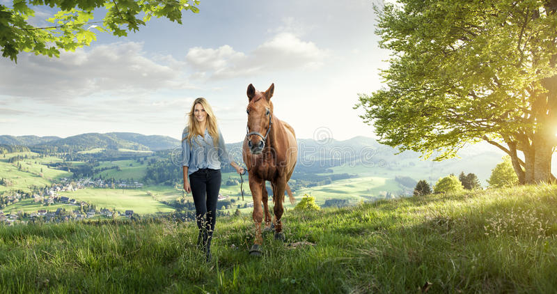 Muchacha rubia hermosa con un caballo en paisajes maravillosos imagen de archivo libre de regalías
