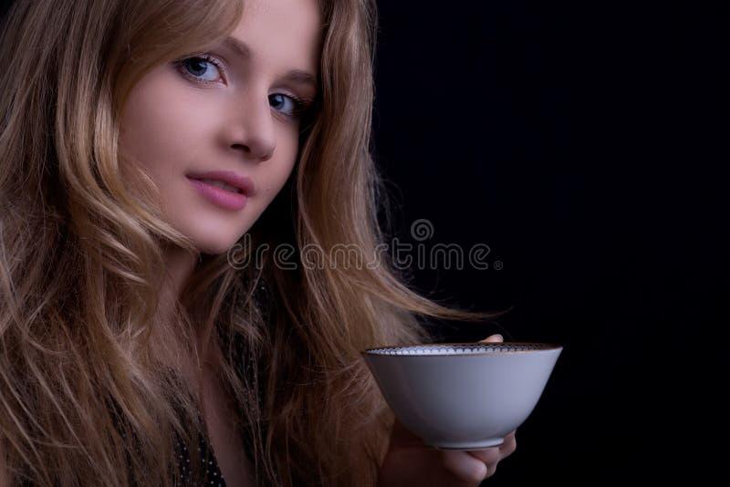 Muchacha rubia hermosa con una taza de té que mira a la cámara imagen de archivo libre de regalías