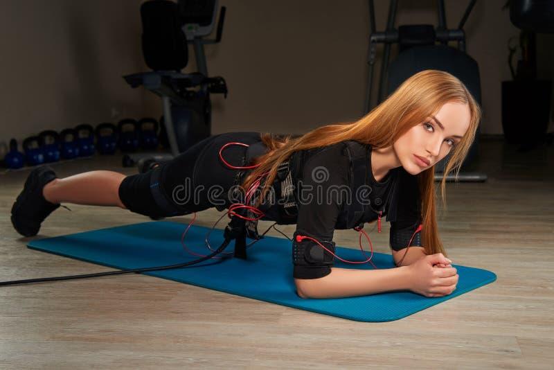 Muchacha rubia hermosa en el traje del ccsme que hace ejercicio del tablón en deportes fotografía de archivo