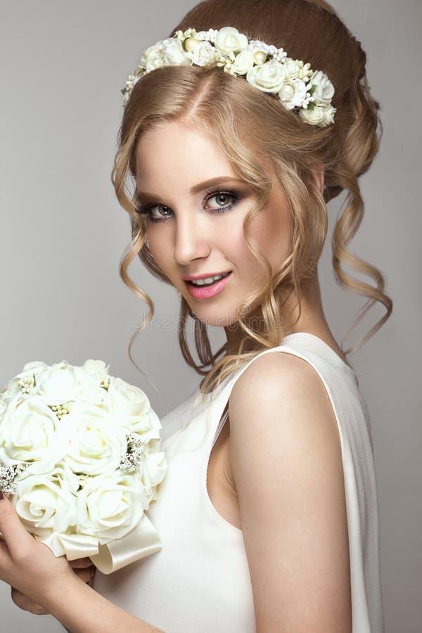 Muchacha rubia hermosa en la imagen de la novia con las flores blancas en su cabeza Cara de la belleza imagenes de archivo