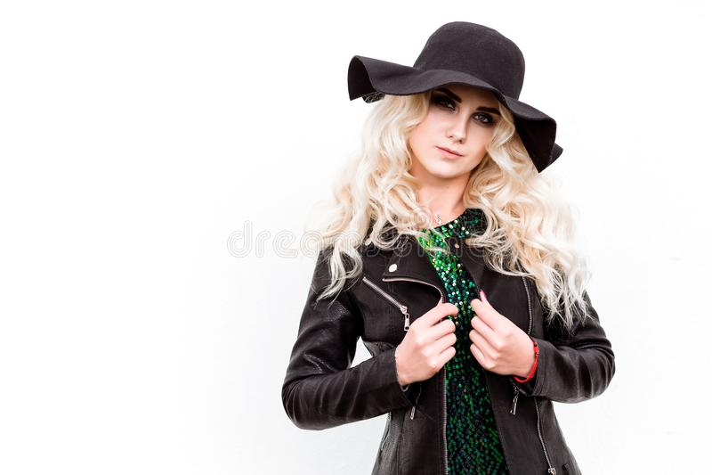 Muchacha rubia hermosa en un vestido brillante y una chaqueta de cuero que presentan contra la pared blanca fotos de archivo