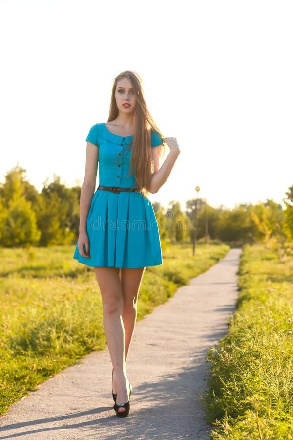 Muchacha rubia hermosa en vestido azul que camina en un camino en un parque imagen de archivo libre de regalías