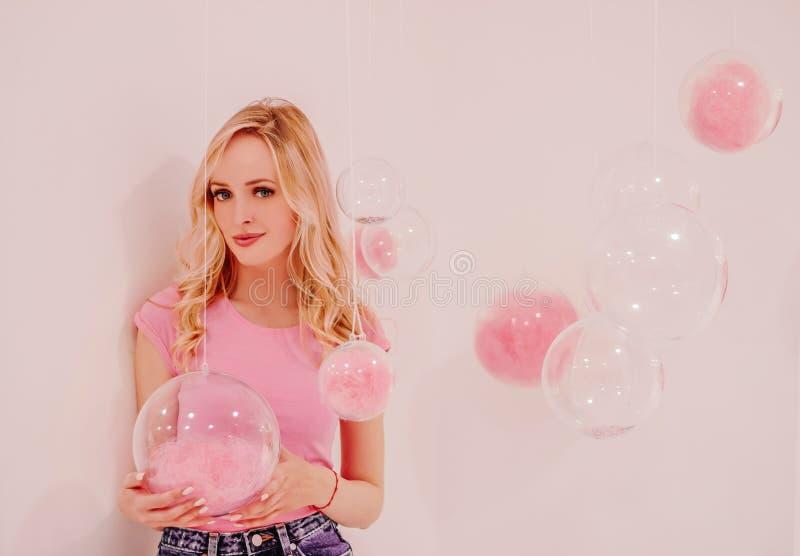 Muchacha rubia hermosa joven en rosa en el fondo blanco con las burbujas transparentes rosadas fotos de archivo libres de regalías