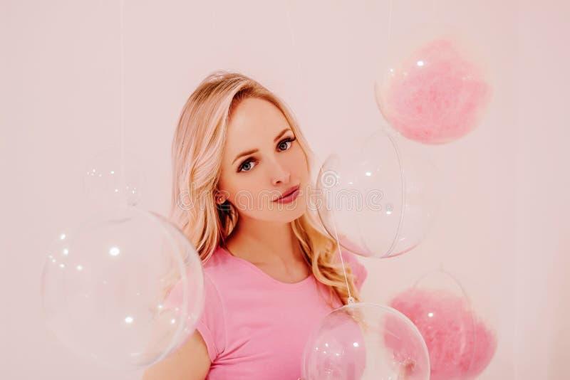 Muchacha rubia hermosa joven en rosa en el fondo blanco con las burbujas transparentes rosadas imágenes de archivo libres de regalías