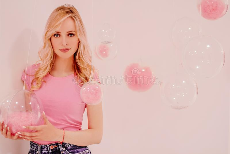 Muchacha rubia hermosa joven en rosa en el fondo blanco con las burbujas transparentes rosadas fotografía de archivo libre de regalías